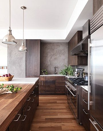 Rich walnut cabinets by Robert Bakes lend a warm, inviting atmosphere to the kitchen of a modern house by designer Alexandra Fazio of Cecil Baker & Partners. The backsplash is hand-troweled plaster, made to look like an old concrete wall.