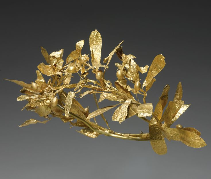 A GREEK GOLD OLIVE WREATH, CIRCA 4TH CENTURY B.C. composed of two olive tree branches bound together at the back with spiral-twisted wire, with lateral shoots of centrally-ribbed leaves and berries attached by long wire stems; the front leaves showing signs of fire damage. Width approx. 9 1/2 in. 24.1 cm.