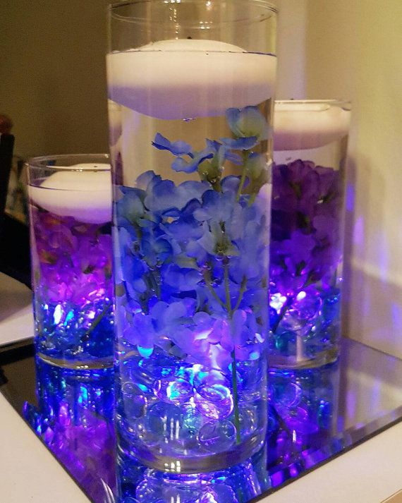 Set of 3 elegant floating candle wedding centerpieces make beautiful table decor for any wedding, bridal shower, baby shower, baptism, birthday party etc.  These cylinder vases with LED lights and blue and purple flowers bring something special to any event and guests are sure to take notice.  This piece also looks great in the house to enhance your home decor and create a beautiful ambiance.  INCLUDES: - 3 vases (9, 7, 5.5) - Clear and light blue glass stones for the bottom of the vases…