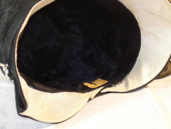This 1920s flapper cloche is in very good wearable condition. A rhinestone pin has been added at some time in the past where another ornament had been. High quality black finely woven straw covers the outside while white straw is under the brim. Chic and classy for the era, this has fits snug with a 21 1/2 inch interior crown. A partial paper label is still intact but no words are on it. This hat shows almost no wear with the lining still in great condition. No stains or holes in the str...