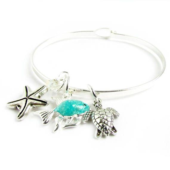 This beach charm bracelet features a pretty blue fish charm, a starfish charm and a tiny sea turtle charm. There is also a sparkling Swarovski Element clear crystal. This adjusts so will fit just about anyone on your gift list. A bangle bracelet to wear year round to keep the summer