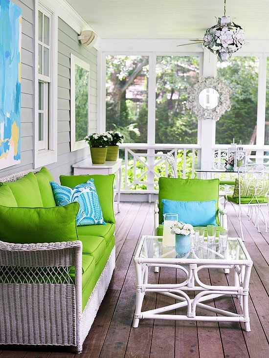 Lime green seat cushions and turquoise accessories infuse this screened porch with youthful energy.