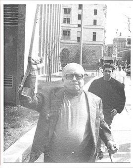 Rare picture of Gambino capo James Failla who tries to hit photographers with his crutches, 1993.