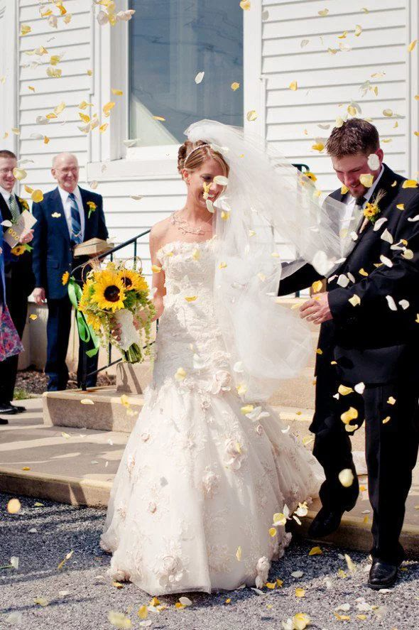 bride with sunflower bouquet and groom in tuxedo leave church while guests throw yellow petals