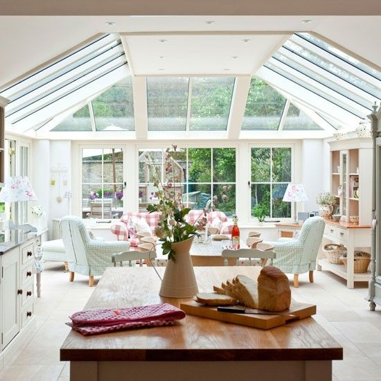 This open-plan conservatory kitchen-diner, is bathed in natural light by the floor-to-ceiling windows and the gingham chair covers and soft green and pnk colour palette creates an English country feel.
