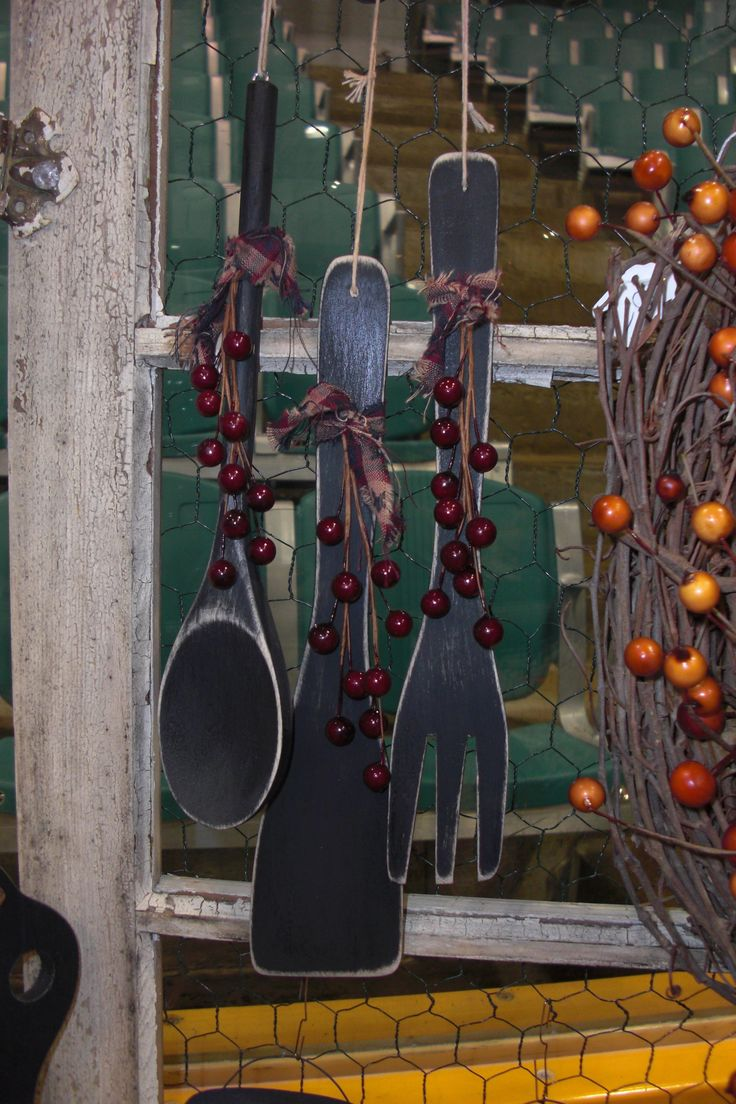 Wooden Spoon Kitchen Decoration  You can get packages of wooden kitchen spoons at the dollar store (usually 4 per pkg) that can easily be painted and made into very cute country kitchen decorations. I spray painted them black, sanded the edges,  and finished off with a homespun tie and dollar store faux berries!