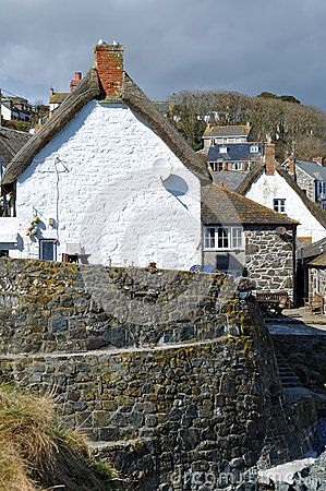 Spring sunshine bathes the whitewashed walls of the thatched cottages clustered around the small inlet of Cadgwith Cove on the Lizard peninsula in Cornwall