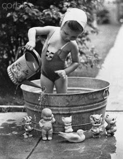Vintage photograph of a little girl in a tub washing her dolls. I spot a kewpie.