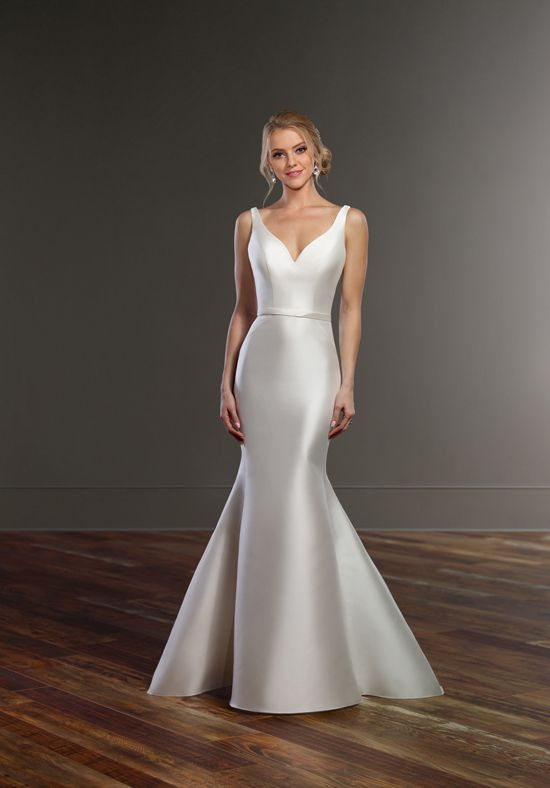 A simple option for the sophisticated bride, this structured wedding dress with double-strap back is a must. The plunging V neckline of this gown - available in five fabric choices - is accented beautifully with solid straps and a coordinating, detachable belt. The skirt of this dress features wide, visible seaming to help shape the gown and a dramatic flare at the knees. A unique double-strap is the highlight of the back of this gown, and is complemented perfectly with a light - yet…