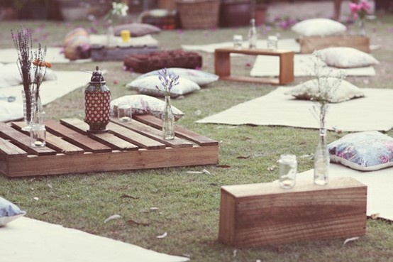 Simple DIY outdoor movie setup - pallet seating, sweet little fresh wildflowers and citronella candles