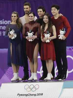 Tessa Virtue and Scott Moir of Canada, centre, celebrate on the podium with second placed Gabriella Papadakis and Guillaume Cizeron of France, left and third placed Maia Shibutani and Alex Shibutani of the United States at right, after winning the gold medal in the ice dance, free dance figure skating final in the Gangneung Ice Arena at the 2018 Winter Olympics in Gangneung, South Korea, Tuesday, Feb. 20, 2018. (AP Photo/David J. Phillip)