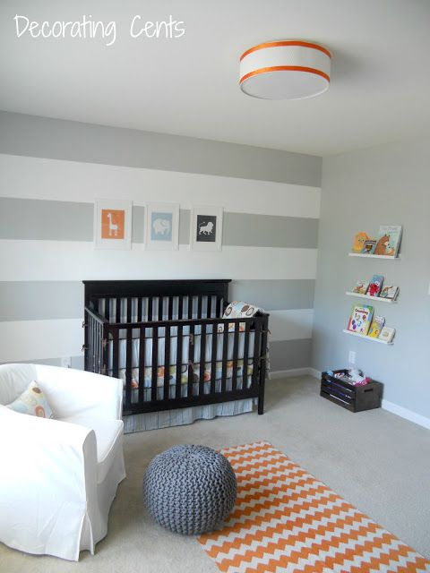 Striped grey white walls, dark crib, light bedding, orange (and navy) accents. Mom can make the crochet ball