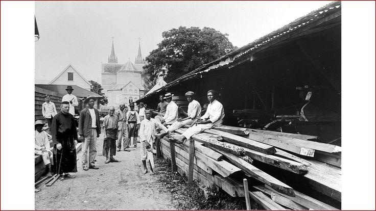 De houtopslag, horende bij de timmerloods van de Rooms Katholieke missie in Paramaribo. Op de achtergrond de houten kathedraal.......voor 1943