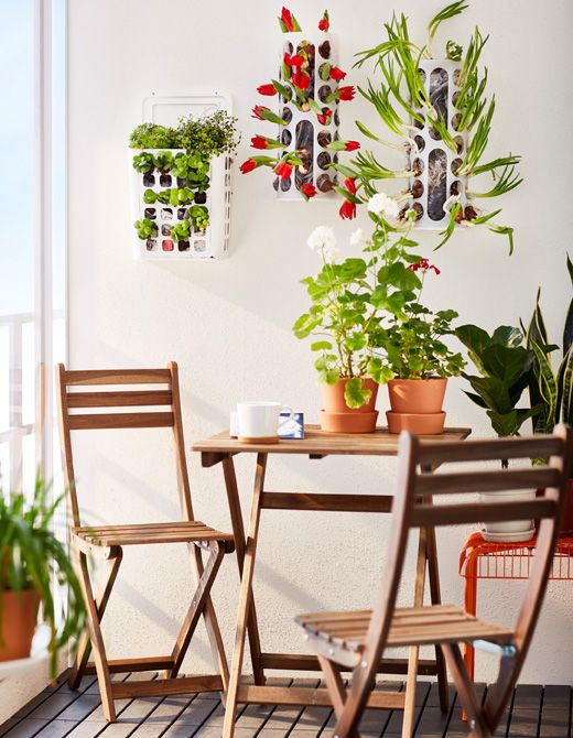 Three VARIERA plastic bag dispensers are hung on the wall of a balcony and used as planters.