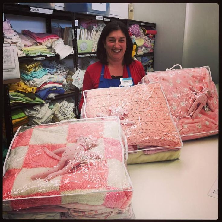 Monique and her beautiful cot linen bundles. Each one has a hand knitted blanket, soft toy, sheets, mattress protectors, gro bags, wraps, and towels - everything you need to welcome a new baby home.