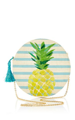 The California-based label serves forth bright, tropical pieces crafted by artisans in South East Asia. This **Kayu** circle clutch is rendered in raffia and features a striped body, pineapple embroidery, a cross-body chain strap, and a zip closure with a tassel detail.