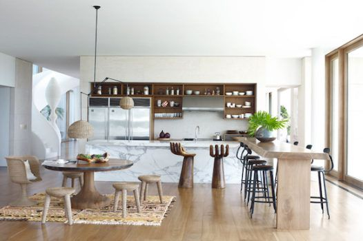 """Kelly Behun says of designing the kitchen of her Long Island, New York, beach house. """"I wanted to have multiple seating options. The 'hand' barstools were purchased with my kids in mind, so they could talk to me while I'm cooking."""" Those """"hand"""" stools were hand-carved in Bali, and the round walnut dining table is a custom piece by Kelly Behun Studio. The wicker and iron hanging lamp is 1940s French, purchased from Van den Akker.  https://www.1stdibs.com/blogs/the-study/neo-victorian-style/"""