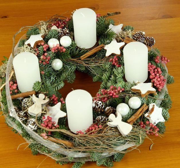 Ein festlicher Kranz mit 35 cm Durchmesser aus Tanne und Lebensbaum gebunden. Dekoriert mit 4 weißen Kerzen, Thymianzweigen, Pfefferbeeren, Kokossternen Schutzengeln und Glaskugeln.