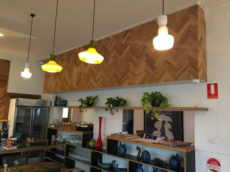 A timber herringbone pattern has cleverly been adhered to this bulkhead to hide a structural necessity and make it an attractive design feature that creates a frame for the the pendant lights positioned in front.
