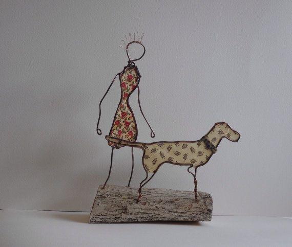 Draad sculptuur van een meisje met haar hond, zijn haar jurk en honden kleur stof en ze zijn op een houten gebaseerd, die is geschilderd met een krijt verf en modge podge te doen om te voltooien. Het meisje is ongeveer 8 iches hoog. Ziet er geweldig uit in een venster of een waar die het opvalt.