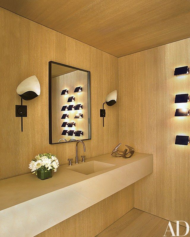 The powder room is lit by a pair of vintage Mouille sconces and a set of Charlotte Perriand CP1 wall lights