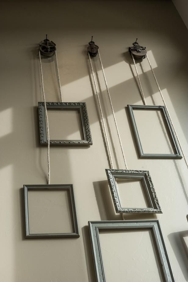 Hanging frames attached to a pulley system tie the upstairs and downstairs living spaces together.