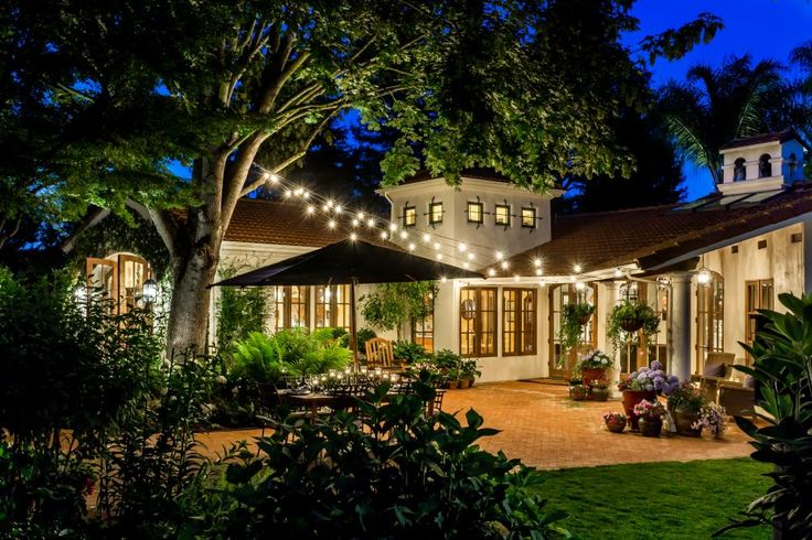 With bistro lights, tiered fountains, and hedges and vines, this patio easily feels like a private retreat in Tuscany. Brick paths wind across the yard, while a pergola and outdoor sitting area invite guests to enjoy a night under the stars.