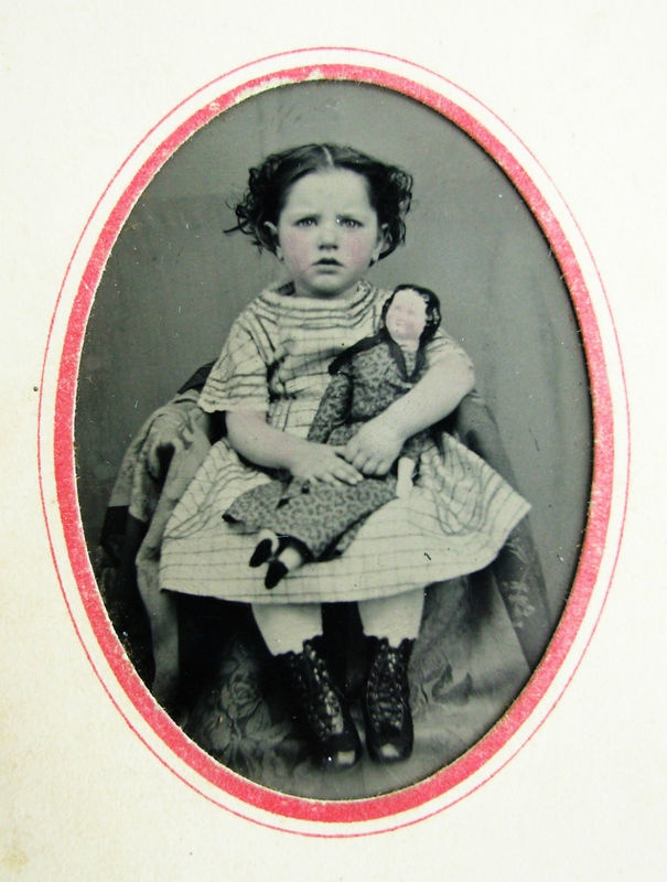 Antique tintype of cute little girl with doll.