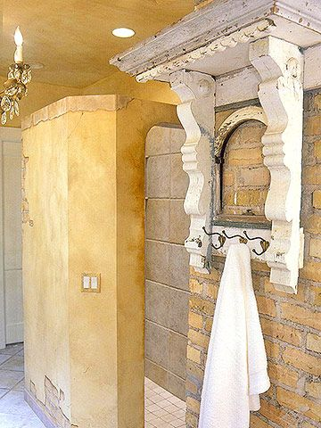 This piece of architectural salvage is transformed into an ornate towel holder by adding metal hooks.