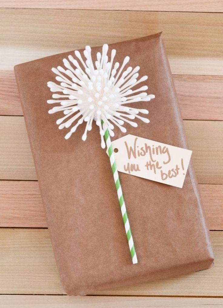 boîte à cadeaux enveloppée de papier brun et décorée d'une fleur DIY en cotons-tiges