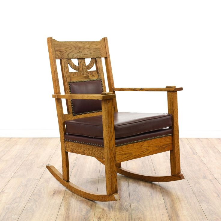 This mission style rocking chair is featured in a solid wood with a rustic oak finish. This craftsman rocker has a carved back with dark red leather upholstered cushions, nailhead trim and joinery details. Stunning statement piece perfect for accenting a room! #americantraditional #chairs #rockingchair #sandiegovintage #vintagefurniture