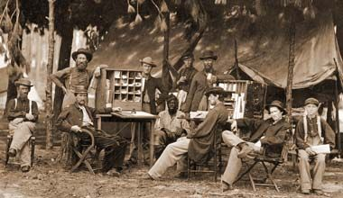 Soldiers relax around the Army Post Office at the quarters of the Chief Ambulance Officer, 9th Army Corps, August 1864, Petersburg, Virginia...
