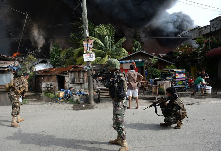 Philippine soldiers aim their rifles at enemy positions during a fire fight with Muslim rebels in Zamboanga City in southern island of Mindanao on September 12, 2013.  AFP PHOTO/TED ALJIBE
