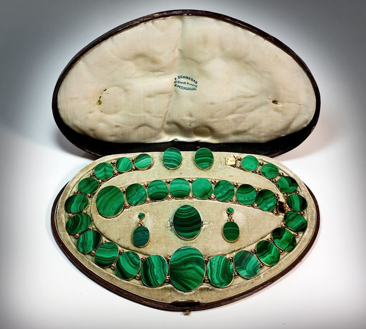 An Exceptionally Rare Victorian Era Russian Malachite and Gold Parure, St. Petersburg 1860s. Apparently, cased Russian 19th century parures exist in single digit numbers. This exceptional parure from the mid Victorian era is complete and in excellent condition for its age. The parure consists of a necklace, a bracelet, a pair of clip-on earpendants, a brooch, and a pair of cufflinks. Finely polished oval plaques of Siberian malachite are set in 14K gold.