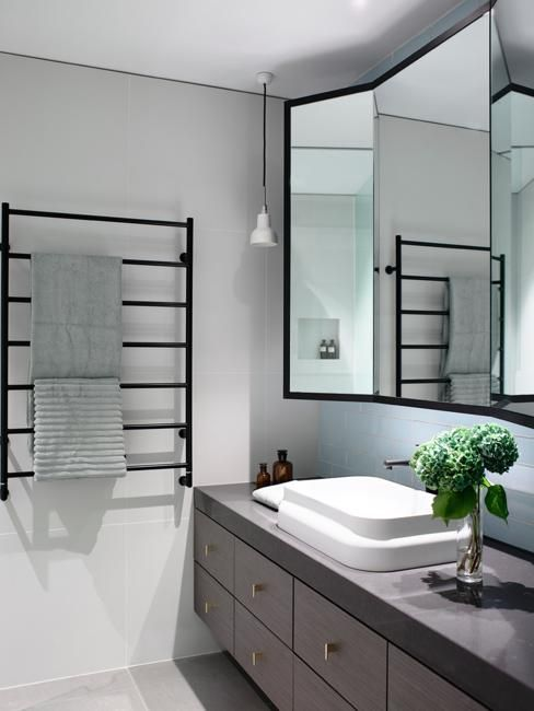 mirrored cabinet in bathroom with wall heater for towels