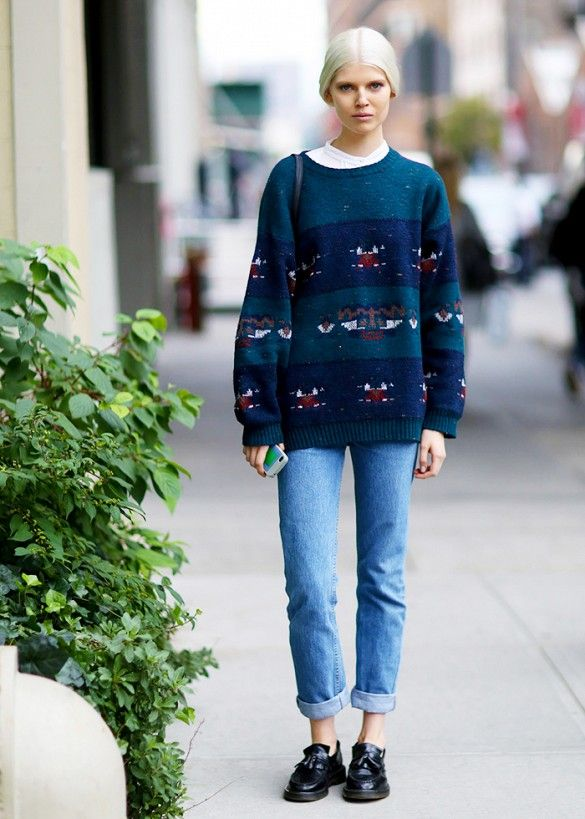 A collared shirt, patterned knit sweater, cuffed jeans, and thick-soled loafers are worn togheter
