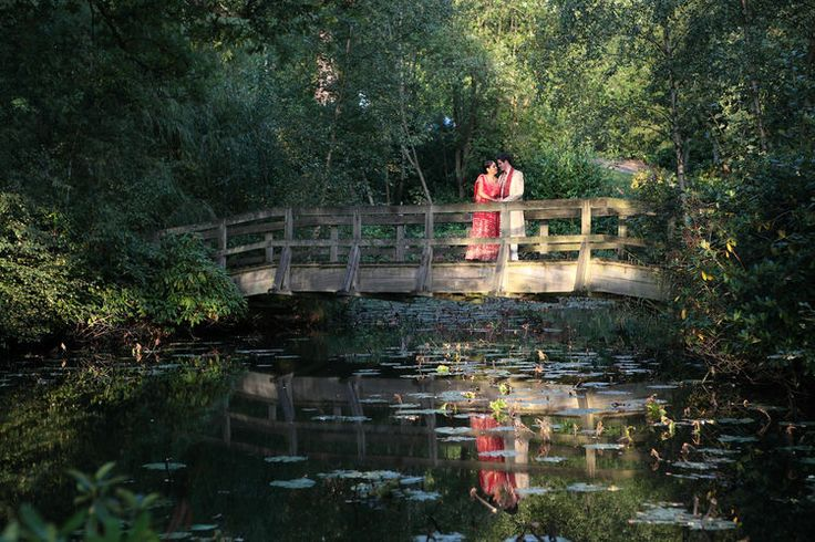 Stunning image of wedded couple on wodden bridge over a pond.