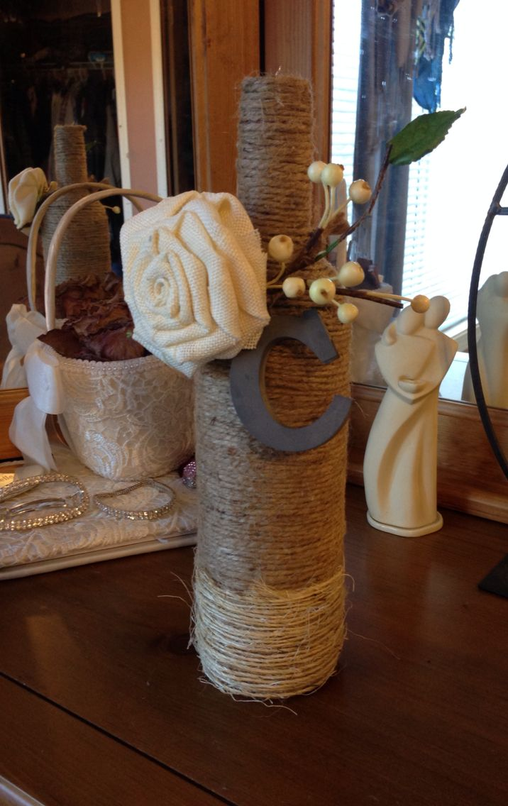 Wine bottle wrapped in twine with a cool vintage metal C for Camille and a burlap flower. All decorations saved from our wedding.