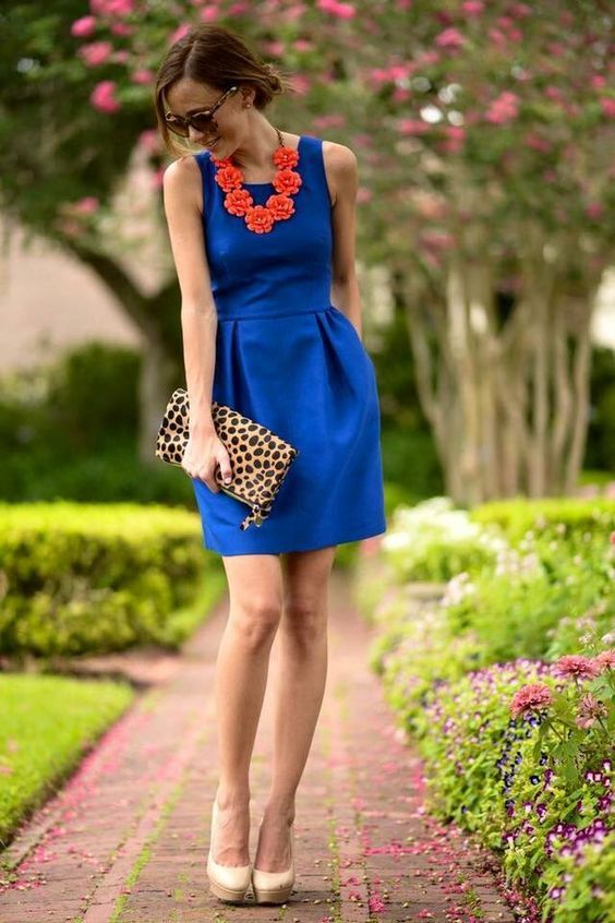 the dress is blue It includes a collar the collar has orange flowers the dress is a women public belleza.facilisimo