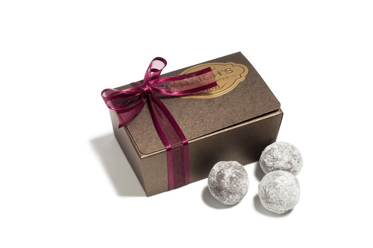 A creamy truffle centre flavoured with French Champagne, hand dipped in dark chocolate and lightly dusted in icing sugar in a ribboned bronze ballotin box.