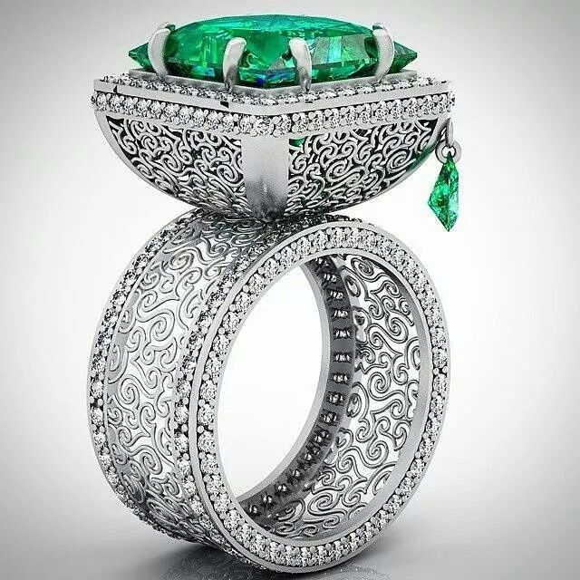 Emerald.    ••••(KO) Did you notice the little dangling Emerald on the side of this stunning ring? To die for !