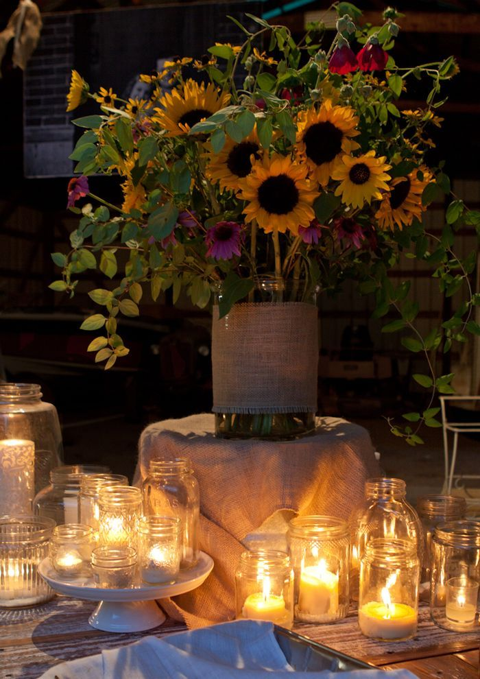 rustic wedding - barn style rehearsal dinner; tealights and votives in all sizes of mason jars; sunflower and vine centerpiece