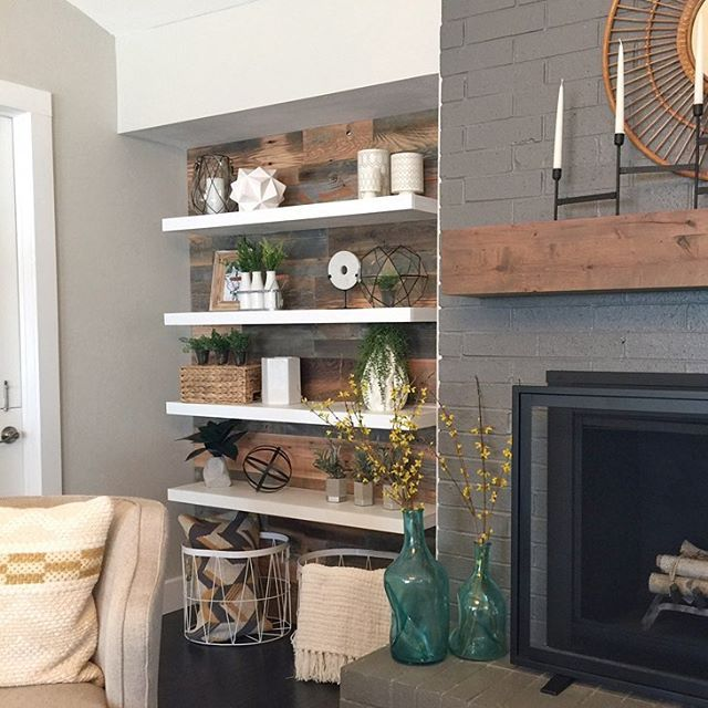 Thin, modern floating shelves and a rustic planked wall for the win ❤️ We knocked down the wall next to this fireplace to add dimension and more storage space in this room. ⭐️Reclaimed barn wood from @reclaimeddesignworks , paint on the fireplace Gauntlet