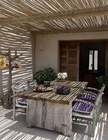 Superbe ambiance sous cette pergola avec son toit en canisse de gros bambou qui filtre le soleil tout en créant un jeu d'ombre et lumière qui s'animent au gré de la brise estivale. On aime l'ambiance total look bois adoptée pour la décoration de cette terrasse avec sa table en bois de récup et le porte manteau fabriqués maison.