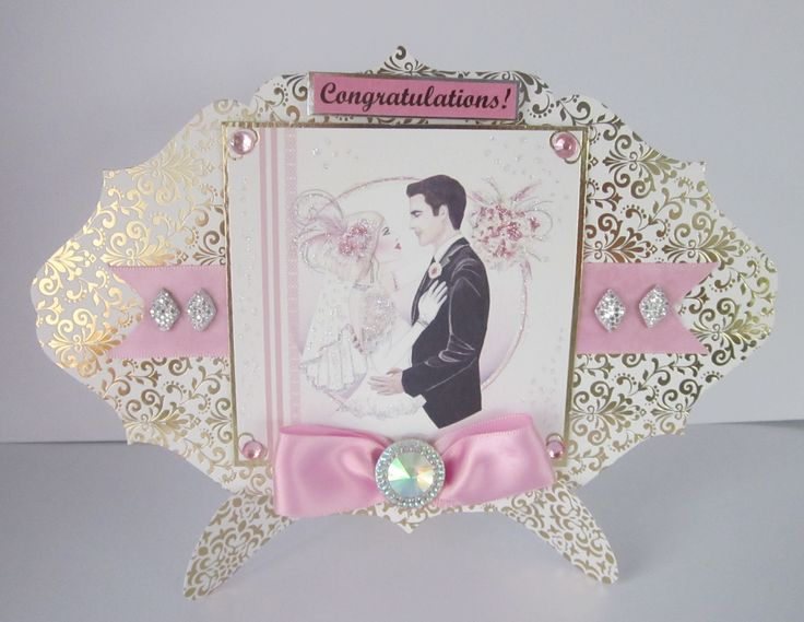 DW63 Congratulations. 8×5 shaped gold foiled card with a separate matching card stand. The picture has been mounted on gold which is affixed to a pink ribbon border. Gems, glitter and a large pink bow added. The stand folds flat for posting. A very unusual card. The envelope has a gold foiled design. £4  …