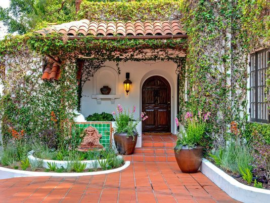 Spanish style- everything about this is a home that I'd love. I'd love the trellises. I'd love the terracotta tiles, the roofs, the little fountain and the wooden door.