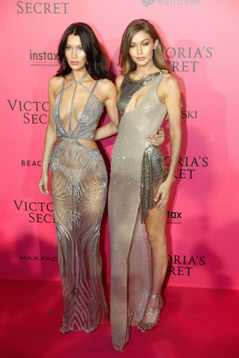 Bella and Gigi Hadid in silver glittery cut out maxi dresses at the 2016 Victoria's Secret show after-party.