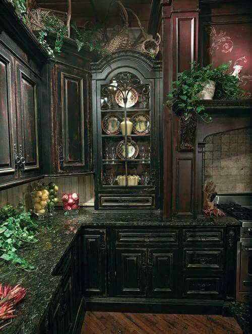 Distressed black ornate kitchen cabinets, dark granite countertops, and plenty of greenery; gothic poetry