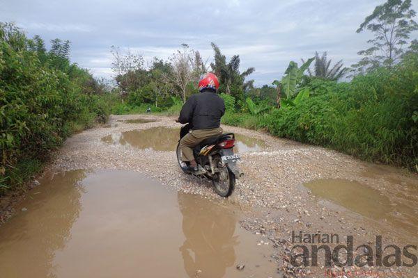 RUSAK BERAT - Seorang pengendara sepeda motor terlihat ekstra hati-hati saat melintas dari badan jalan yang rusak berat di Dusun Pandan Bulu...