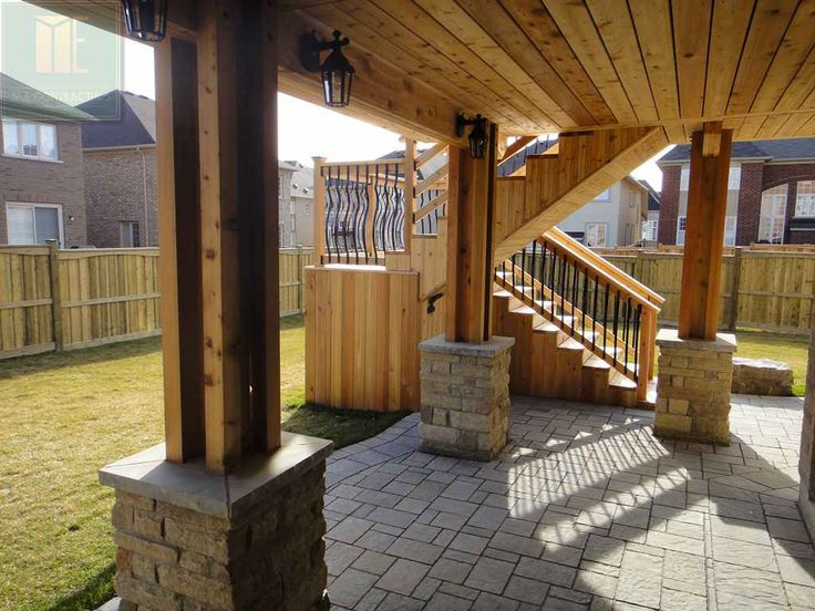 2 level cedar deck with wrought iron railings, pergola and stone walkout basement